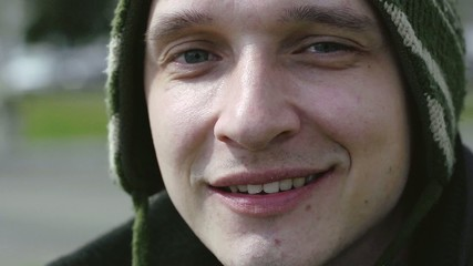 Young man smiles on camera closeup