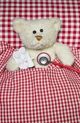Patient: Kranker Teddybär liegt mit Grippe im Bett