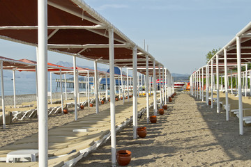 The beach in the resort area with sun beds and umbrellas