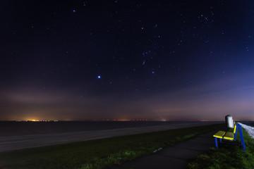 Sitzbank am Ufer und leuchtender Sternenhimmel
