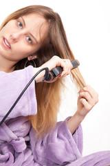 jeune femme en robe de chambre qui lisse ses cheveux