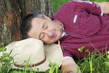 Tired man resting under the tree: