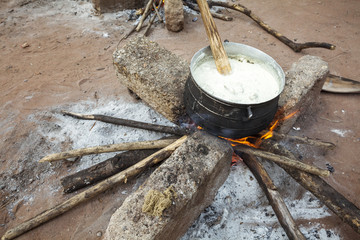 Preparing banku on a fire, Africa