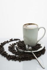 Tasse Kaffee auf Kaffeebohnen auf weißem Untergrund