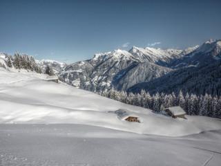 eingeschneite Schihütte in den Alpen in HDR