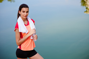 Beautiful girl in bright sportswear resting after the jogging