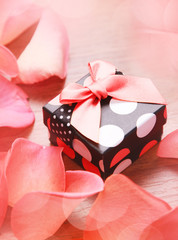 Gift box with bow and rose petals