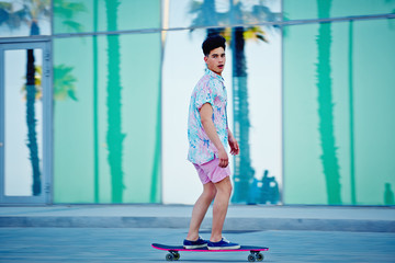 Young cool guy in bright clothes riding on longboard