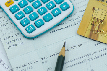close up bank statement with calculator and credit card