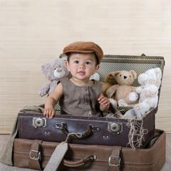 Kind im Koffer mit Teddybären
