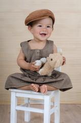 Kind auf einem Stuhl mit Teddy