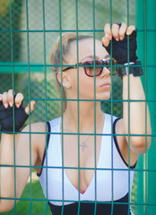 beautiful athletic girl in sunglasses looking through the bars