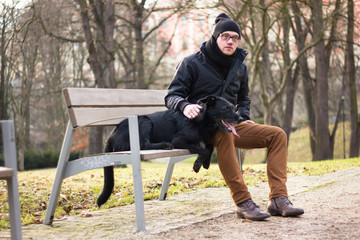 Best friends: Young man sitting with his dog on a bench