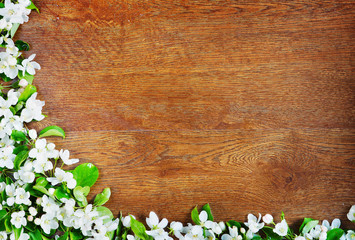 Decorative corner made of apple flowers over wooden background