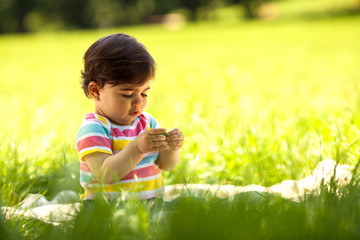 Baby girl sitting on grass and playing with flowers.