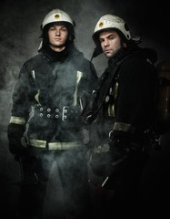 Two firefighters with axes in a smoke