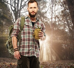 Handsome traveler with backpack and flask in autumnal forest