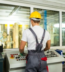 Operator wearing safety hat in a factory control room