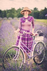 Woman in purple dress with retro bicycle in lavender field