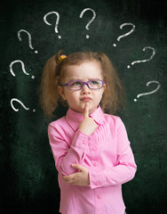 Child in eyeglasses standing near school blackboard with many qu