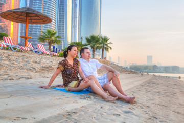 Couple watching romantic sunrise on the beach of Abu Dhabi
