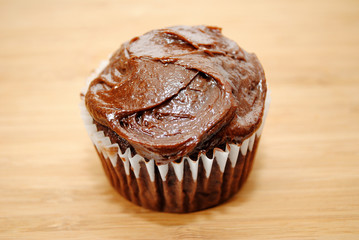 Chocolate Frosted Cupcake on a Wooden Background