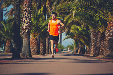 Muscular athletic man running on the jogging tracK