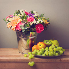 Flower bouquet and fresh fruits on wooden table