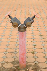 red rusty metal industrial water pipes with a valve.