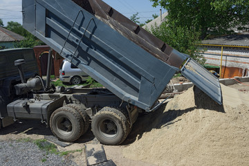 Tip truck is dumping sand in the backyard.