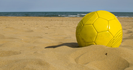 Yellow ball on the sand ready to be kicked