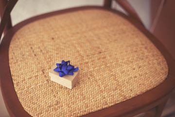 present box with blue ribbon and vintage chair