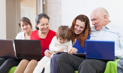 Happy family enjoys on sofa with few laptops