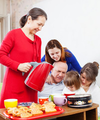 Mature woman pours tea for her family