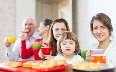 family having tea with cakes
