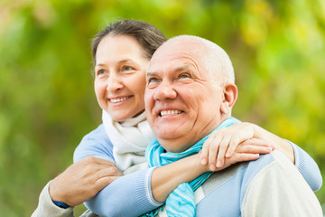 Portrait of mature couple against blured trees