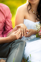 groom putting golden ring in brides hand at park