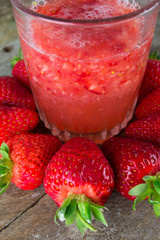 Fresh strawberry drink on wood background