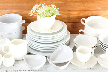 Different tableware on shelf, on wooden background