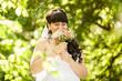 portrait of young brunette bride sniffing wedding bouquet at par