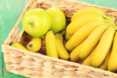 Leinwandbild Motiv Bunch of mini bananas in wicker box on color wooden background