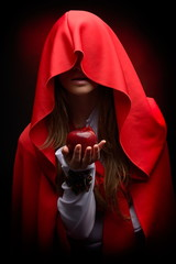 beautiful woman with red cloak hoding apple
