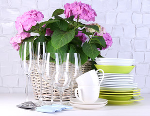 Blooming hydrangea and utensils on table on grey wall