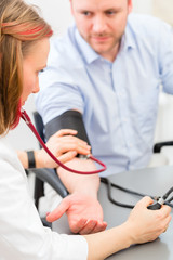 Doktor behandelt Patient in Arztpraxis