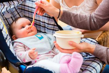 Mutter füttert Baby bei Hebamme