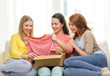smiling teenage girls opening cardboard box
