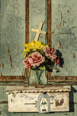 Rustic old doorway flowers and cross