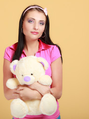 Childish woman infantile girl in pink hugging teddy bear toy