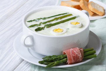 Asparagus soup with eggs in white bowl