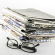 stack of newspaper with glasses